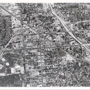 Santa Fe Railroad tracks cut diagonally across photo from east to west.  Huntington Drive bisects photo from east to west approximately at center of photo.  Arcadia County Park appears in lower left corner, showing baseball diamond.  Santa Anita Wash is shown on right side of photo.