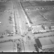 Aerial view of what appears to be either an informal horse show or possible horse sale with a great number of people in attendance.  The location has been identified as near intersection of Las Tunas Drive and (with what seem to be railroad tracks in center) Temple City Boulevard.  The building (we see only roof) in the lower left corner is Vernon's Pharmacy.  The letters VGS can be seen over front entry.  There are probably about 100 autos parked nearby. (There is another photo of this event, #539.)
