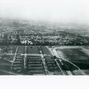 "Looking east over barracks and main building at Ross Field.  Tree-lined street cutting across photo at far side of field is Santa Anita Avenue.  The oval of the race track built by E.J.""Lucky"" Baldwin and which opened in 1907 can clearly be seen on right.  Broad E/W street seen on far left is Huntington Drive."