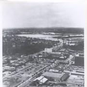 Aerial looking west from a position just east of First Avenue and just north of Wheeler Avenue.  Large white barn-like roof is San Gabriel Valley Lumber Co. building.  This later became the Sawmill Restaurant and in the early 1990's became Sports Rock Cafe. Directly opposite, is cleared land where Arcadia Public Library, Fire and Police were previously located.  Today there is a Medical Building on the site (65 N. First Avenue). Santa Anita Park and parking lot are seen in the distance.